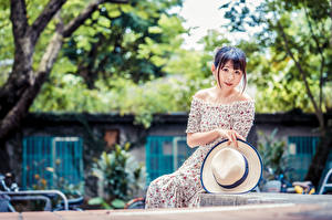 Pictures Asian Blurred background Sitting Frock Hat Staring female