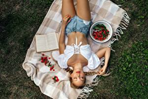 Images Berry Grass From above Book Bowl Esting Braid hair Shorts Hands young woman