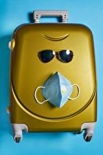Photo Creative Masks Coronavirus Colored background Suitcase Eyeglasses