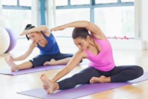 Fotos Fitness Bokeh Pose Brünette Zwei Sitzend Hand Bein Unterhemd Dehnübungen junge frau Sport