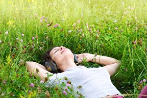 Picture Grass Headphones Hands Lying down Relax young woman
