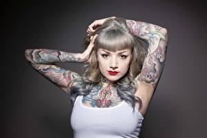 Fotos Grauer Hintergrund Blick Hand Tätowierung Make Up Piercing junge frau