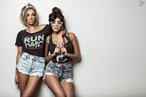 Fotos Grauer Hintergrund Zwei Blond Mädchen Brünette Starren Umarmung Hand Shorts