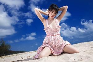 Fotos Asiatisches Sand Sitzt Kleid Blick Posiert junge Frauen