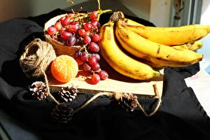 Image Bananas Grapes Mandarine Cutting board Conifer cone Food
