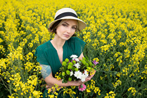 Pictures Fields Rapeseed Bouquet Hat Staring Frock Alena young woman Nature