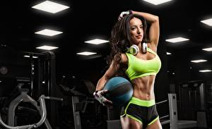 Pictures Fitness Brunette girl Pose Headphones Hands Glove Ball Belly Shorts young woman Sport
