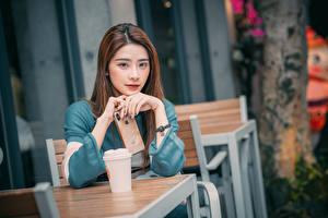 Bilder Asiatische Apple Hand Smartphone Blick Unscharfer Hintergrund Tisch Braunhaarige Mädchens