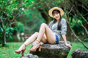Fondos de escritorio Asiática Piedra Sentado Pierna Pantalón corto Sombrero de Camisa Cabello negro Nia Contacto visual Pose mujer joven