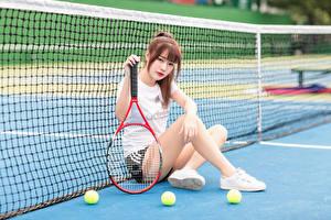 Fotos Asiatisches Tennis Sitzend Sportnetze Bein Starren Ball junge frau