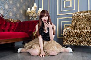 Bilder Asiatisches Braunhaarige Sitzt Kleid Hand Starren junge Frauen