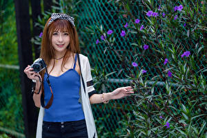 Desktop wallpapers Asiatic Brown haired Smile Camera Sleeveless shirt Glance young woman