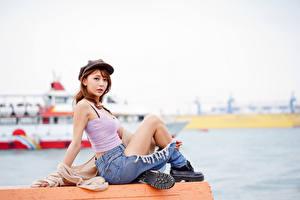 Bilder Asiatische Sitzt Baseballkappe Unterhemd Bein Boots Schuhsohle junge Frauen