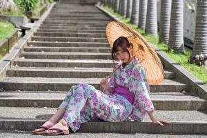 Fotos Asiatisches Stiege Sitzend Kimono Regenschirm Mädchens