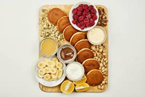 Pictures Pancake Raspberry Nuts Bananas Lemons Honey Chocolate Gray background Cutting board Cream