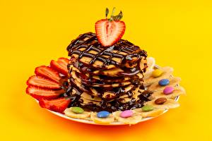 Hintergrundbilder Eierkuchen Erdbeeren Dragee Schokolade Bananen Teller Farbigen hintergrund Lebensmittel