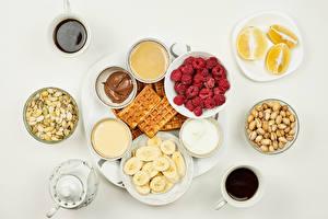 Photo Coffee Raspberry Nuts Waffles Chocolate Bananas Orange fruit Gray background Cup Cream