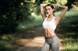 Images Fitness Bokeh Posing Brunette girl Glance Hands Belly young woman