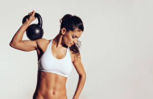 Images Fitness Gray background Brunette girl Belly Hands Kettlebell young woman