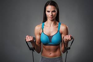 Pictures Fitness Gray background Brunette girl Staring Hands Belly Girls