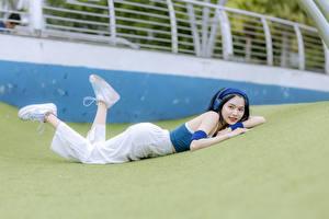 Bureaubladachtergronden Aziaten Brunette meisje Liggend Koptelefoon Benen Sportschoen Jonge_vrouwen