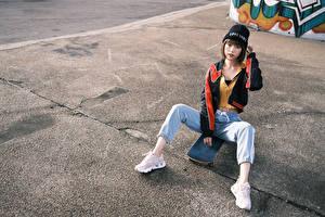 Fotos Asiatische Skateboard Sitzend Jeans Mütze Sportschuhe Blick Mädchens