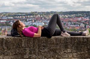 Bureaubladachtergronden Liggende Jeans T-shirt Rusten jonge vrouw
