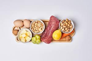Tapety na pulpit Produkty mięsne Orzechy Cytryny Papryka Szare tło Deska do krojenia Jajka Jedzenie